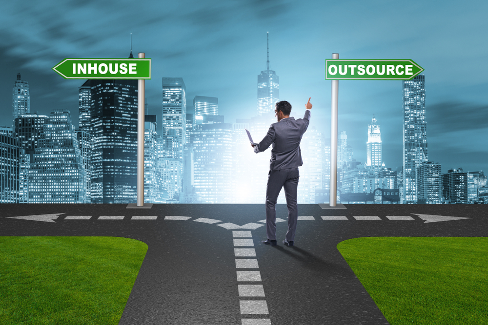 A man is pointing his finger on the word outsource